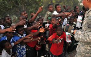 Survivors of Tuesday's earthquake extend their arms as U.S. troops with the 82nd Airborne Division distribute water in Port-au-Prince, Sunday, Jan. 17, 2010.