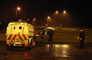 Police officers cordon off the area near Lismore Manor, Craigavon, Northern Ireland, Tuesday, March 10, 2009. A large security presence has begun after a Police Service of Northern Ireland officer was shot dead by suspected Irish Republican terrorists. (AP Photo/Peter Morrison)