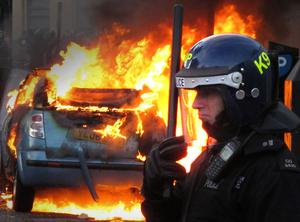 LONDON, ENGLAND - AUGUST 08:  A police officer in riot gear stands near a burning car in Hackney on August 8, 2011 in London, England. Pockets of rioting and looting continues to take place in various boroughs of London this evening, as well as in Birmingham, prompted by the initial rioting in Tottenham and then in Brixton on Sunday night. It has been announced that the Prime Minister David Cameron and his family are due to return home from their summer holiday in Tuscany, Italy to respond to the rioting. Disturbances broke out late on Saturday night in Tottenham and the surrounding area after the killing of Mark Duggan, 29 and a father-of-four, by armed police in an attempted arrest on August 4.  (Photo by Peter Macdiarmid/Getty Images)