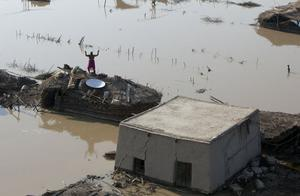 A man waves from the roof of a building, surrounded by flood water