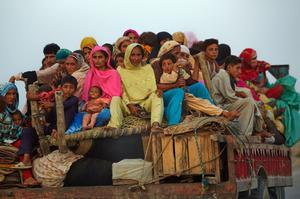 Villagers displaced from their homes by flooding sit on their belongings as they evacuate