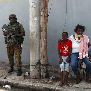 Residents gather outside a house as a soldier stands guard in Jamaica (AP)
