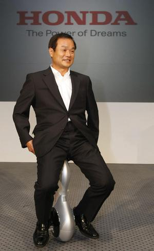 "Honda Motor Co. President Takanobu Ito poses for photographers as he demonstrates Honda's new ""personal mobility"" device at a press conference in Tokyo, Japan, Thursday, Sept. 24, 2009"