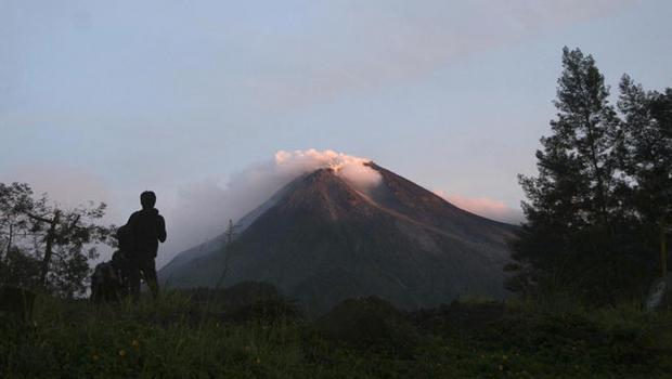 A villager watches Mount Merapi in Kaliadem, Yogyakarta, Indonesia, Tuesday, Oct. 26, 2010. Indonesia's most volatile volcano started erupting Tuesday, after scientists warned that pressure building beneath its dome could trigger the most powerful eruption in years. (AP Photo)