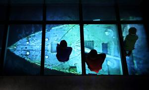BELFAST, NORTHERN IRELAND - MARCH 27:  Visitors look down on a projection showing images of the wreck of the Titanic on the seabed at the Titanic Belfast visitor attraction on March 27, 2012 in Belfast, Northern Ireland. The Titanic Belfast Experience is a new £90 million visitor attraction opening on March 31, 2012. One hundred years ago the maiden voyage of the ill-fated passenger liner Titanic sank after hitting an iceberg in the Atlantic on the night of April 14, 1911 with the loss of 1517 lives.  (Photo by Peter Macdiarmid/Getty Images)