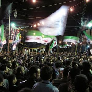Syrians wave revolutionary flags and chant slogans at a night protest against President Bashar Assad (AP)