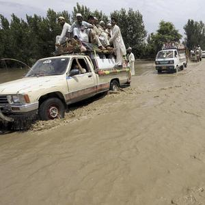 Vehicles drive through a flooded road in Charsadda, in Pakistan's northwest (AP)