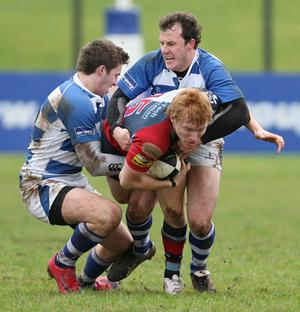 Tight grip: Quins' player Rory Scholes is held by Dungannon