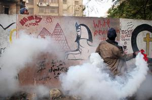 An Egyptian protester throws a tear gas canister as a man, left, looks on during clashes with Egyptian riot police in Cairo, Egypt, Monday, Nov. 21, 2011. Security forces fired tear gas and clashed Monday with several thousand protesters in Cairo's Tahrir Square in the third straight day of violence that has killed dozens of people and has turned into the most sustained challenge yet to the rule of Egypt's military. (AP Photo)
