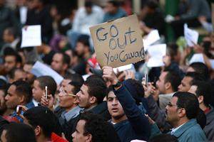 CAIRO, EGYPT - JANUARY 30:  A man in Tahrir Square holds a placard calling for President Hosni Mubarak to ''go out'' on January 30, 2011 in Cairo, Egypt. As President Mubarak struggles to regain control after five days of protests he has appointed Omar Suleiman as vice-president. The present death toll stands at 100 and up to 2,000 people are thought to have been injured during the clashes which started last Tuesday. Overnight it was reported that thousands of inmates from the Wadi Naturn prison had escaped and that Egyptians were forming vigilante groups in order to protect their homes after Police were nowhere to be seen on the streets. Broadcasts from the Al-Jazeera television network via an Egyptian satellite have now been halted.  (Photo by Peter Macdiarmid/Getty Images)