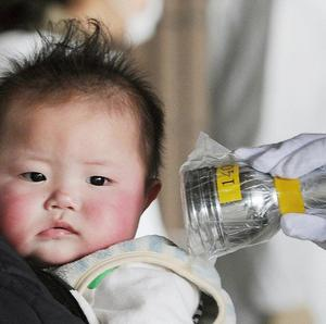 A baby is screened for leaked radiation from the damaged Fukushima nuclear facilities (AP)