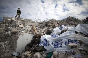 A member of an Israeli rescue team and a dog search through a pile of dead bodies for survivors at the GOC university on January 19, 2010