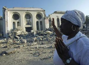 A Haitian woman prays alongside the destroyed National Cathedral in Port au Prince, Haiti, Tuesday, Jan. 19, 2010.