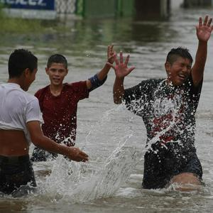 Children play in a flooded street after Hurricane Alex hit the area in Matamoros, northeastern Mexico, on the border with Texas