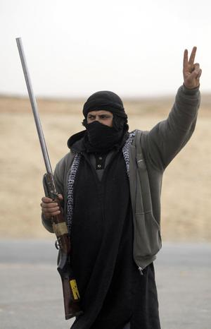 A Libyan anti-government fighter flashes the V-sign as the mans a checkpoint in the outskirts of the southwestern town of Nalut, Libya,  Monday, Feb. 28, 2011. The town is currently in control of the Libyan anti-government forces. (AP Photo/Lefteris Pitarakis)