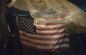 """PORTLAND, OR - NOVEMBER 13:  An American flag has an ironic """"closed"""" sign, as seen in Occupy Portland November 13, 2011 in Portland, Oregon.  In spite of an eviction notice for early Sunday morning, Portland police delayed closing two downtown parks early today as thousands of people converged to support the Occupy Portland movement.(Photo by Natalie Behring/Getty Images)"""