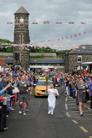 Victoria Walsh carrying the Olympic flame during the torch relay leg between Dervock and Portrush