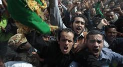 In this image taken during an organized trip by the Libyan authorities, Libyan supporters of Moammar Gadhafi, some of whom came from Tripoli, take part in a staged demonstration in Ban-Waled, home of the Warfallah tribe, 160kms (100 miles) south east of Tripoli, Libya, Wednesday March 23, 2011. International air strikes forced Moammar Gadhafi's tanks to roll back from the western city of Misrata on Wednesday, giving respite to civilians who have endured more than a week of attacks and a punishing blockade.(AP Photo/Jerome Delay)