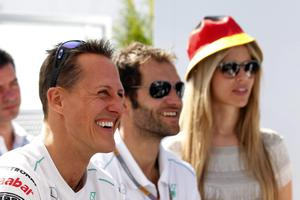Mercedes Grand Prix driver Michael Schumacher of Germany smiles as he watches on a screen, the Euro 2012 soccer match between Germany and Portugal , after the qualifying session at the Gilles Villeneuve racetrack, in Montreal, Canada, Saturday, June 9, 2012. The Formula one race will be held on Sunday. (AP Photo/Luca Bruno)