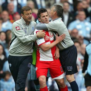 Joey Barton (centre) has been bailed over an incident outside a Liverpool club