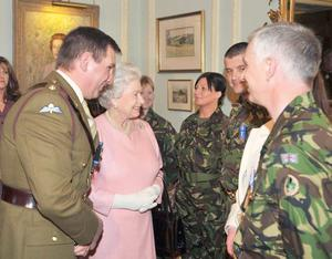 Britain's Queen Elizabeth II (centre) at Hillsborough Castle in Northern Ireland, where she met around 300 members and workers from the Territorial Army during a reception to mark the group's centenary. PRESS ASSOCIATION Photo.