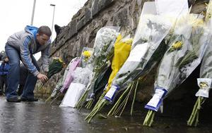 A man leaves flowers near Massereene army barracks, in Antrim, west of Belfast, Northern Ireland, Sunday, March, 8, 2009. Suspected IRA dissidents opened fire on British troops and pizza delivery men outside a Northern Ireland army base, killing two soldiers and wounding four other people. Police said Sunday the attackers fired on their victims again as they lay wounded on the ground. (AP Photo/Peter Morrison)