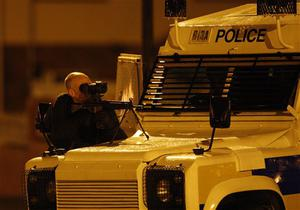 A Police Service of Northern Ireland officer aims his rifle as he takes up position near Lismore Manor, Craigavon, Northern Ireland, Tuesday,March, 10, 2009. A large security presence has begun after a Police Service of Northern Ireland officer was shot dead by suspected Irish Republican terrorists.  (AP Photo/Peter Morrison)