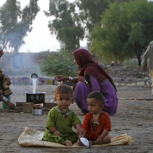 A Pakistani family waits to flee from an area due to heavy flooding in Qadirpur near Sukkur