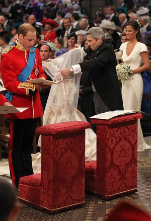 LONDON, ENGLAND - APRIL 29: Prince William stands beside his bride Catherine Middleton as her father Michael Middleton helps her with her veil on April 29, 2011 in London, England.  The marriage of Prince William, the second in line to the British throne, to Catherine Middleton is being held in London today. The marriage of the second in line to the British throne is to be led by the Archbishop of Canterbury and will be attended by 1900 guests, including foreign Royal family members and heads of state. Thousands of well-wishers from around the world have also flocked to London to witness the spectacle and pageantry of the Royal Wedding.  (Photo by Dominic Lipinski - WPA Pool/Getty Images)