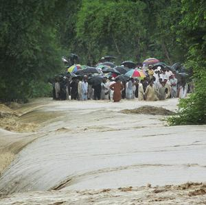 People wait to cross a flooded road in Bannu, north-western Pakistan.(AP)