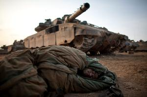 ISRAEL/GAZA BORDER, ISRAEL- NOVEMBER 19:  (ISRAEL OUT) An Israeli soldier sleeps next to tanks in a deployment area on November 19, 2012 on Israel's border with the Gaza Strip. The death toll has risen to at least 85 killed in the air strikes, according to hospital officials, on day six since the launch of operation 'Pillar of Defence.'  (Photo by Uriel Sinai/Getty Images)