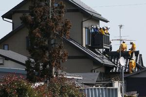 SENDAI, JAPAN - MARCH 14:  Members of a rescue team climb into a house after a warning of tsunami is issued after a 9.0 magnitude strong earthquake struck on March 11 off the coast of north-eastern Japan, on March 14, 2011 in Sendai, Japan. The quake struck offshore at 2:46pm local time, triggering a tsunami wave of up to 10 metres which engulfed large parts of north-eastern Japan. The death toll is currently unknown, with fears that the current hundreds dead may well run into thousands.  (Photo by Kiyoshi Ota/Getty Images)