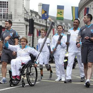 A torchbearing team carries the Paralympic Flame on the Torch Relay leg through Westminster