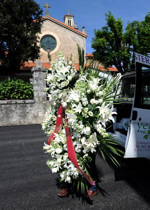 PEDRENA, SPAIN - MAY 10:  A woman carries a floral tribute backdropped by the parish church where tomorrow's funeral service for legendary Spanish golfer Seve Ballesteros will be held, on May 10, 2011 in Pedrena, Spain.  (Photo by Jasper Juinen/Getty Images)