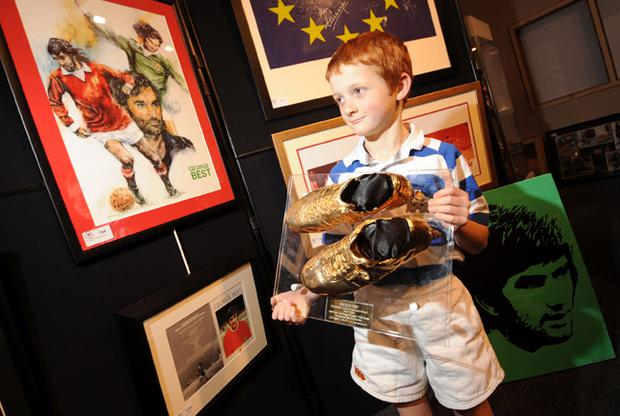 Best Fan - 7 year old Luke McMullan from Dungannon (dressed in his school rugby kit) holding a cast from George Best's original match worn boots, pictured amongst Best memorabilia at Wilsons Auction house today. There are 110 lots of George Best memorabilia available, collected by Dickie Best over a period of 40 years.