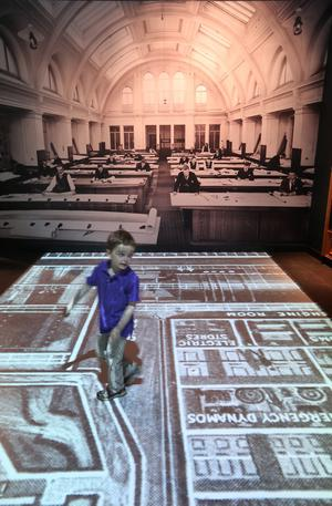 BELFAST, NORTHERN IRELAND - MARCH 27:  A boy  runs across an interactive projection of the Harland and Wolff drawing Office at the Titanic Belfast visitor attraction on March 27, 2012 in Belfast, Northern Ireland. The Titanic Belfast Experience is a new £90 million visitor attraction opening on March 31, 2012. One hundred years ago the maiden voyage of the ill-fated passenger liner Titanic sank after hitting an iceberg in the Atlantic on the night of April 14, 1911 with the loss of 1517 lives.  (Photo by Peter Macdiarmid/Getty Images)