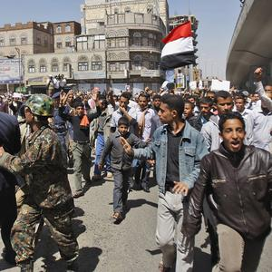 Yemeni police block the way as anti-government protesters call for the resignation of President Ali Abdullah Saleh (AP)
