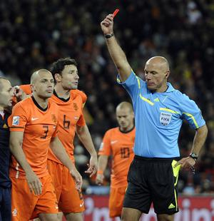 Referee Howard Webb of England, right, shows the red card to Netherlands' John Heitinga, left, during the World Cup final soccer match between the Netherlands and Spain at Soccer City in Johannesburg, South Africa