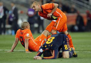 Netherlands' Wesley Sneijder, standing right, helps his teammate Nigel de Jong, left, stretch as Spain's Xavi Hernandez reacts during the World Cup final soccer match between the Netherlands and Spain at Soccer City in Johannesburg