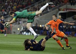 Spain goalkeeper Iker Casillas, left, makes a save above Netherlands' Robin van Persie, right, and Spain's Carles Puyol, bottom, during the World Cup final soccer match between the Netherlands and Spain at Soccer City in Johannesburg, South Africa