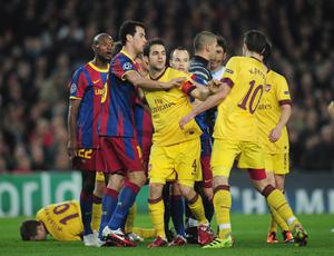 BARCELONA, SPAIN - MARCH 08:  Arsenal captain Cesc Fabregas steps in between Sergio Busquets of Barcelona and team-mate Robin van Persie during the UEFA Champions League round of 16 second leg match between Barcelona and Arsenal at the Nou Camp Stadium on March 8, 2011 in Barcelona, Spain.  (Photo by Shaun Botterill/Getty Images)
