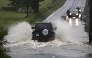 NI FLOODS 22 JUNE 2012...Vehicles attempt to travel on the Glenkeen Road between Coleraine and Garvagh as heavy rain continues to fall as already over 2ft of water lies on the road.. Pic Steven McAuley/Kevin McAuley Photography Multimedia
