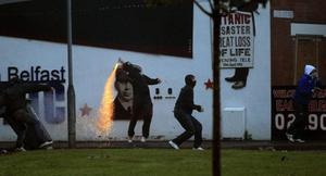 Loyalist rioter  throws a firework towards the mainly Catholic Short Strand area of East Belfast, Northern Ireland, Tuesday, June, 21, 2011