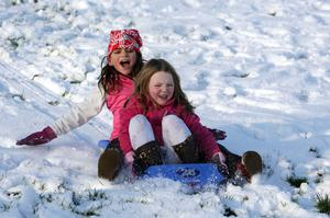 Nisha Stevenson and Sophia Thomasius sleighing in the snow at Brooke Park, Derry