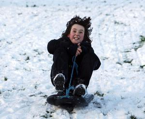 10 years-ol Pablo O'Connor bounding along in his sleigh on the snow at Brooke Park, Derry