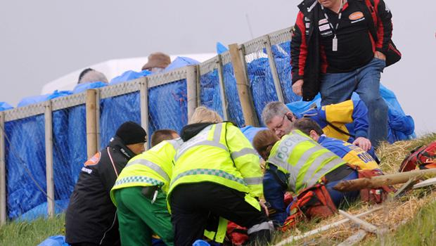 Steve Plater's father Trevor looks on as medics treat his son after he crashed at Quarry Hill during yesterday's practice for the Relentless North West 200
