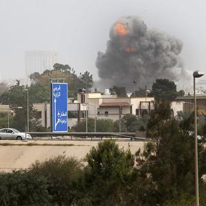 Smoke and dust rises following a Nato airstrike in Tripoli, Libya (AP)