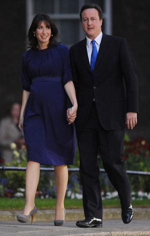 Britain's new Prime Minister David Cameron and his wife, Samantha, stand in Downing Street after an audience with The Queen