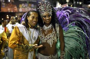 Brazilian soccer player Ronaldinho, left, embraces Cris Vianna, queen of the drums' section of the Grande Rio samba school, while posing for a photo during carnival celebrations at the Sambadrome in Rio de Janeiro, Brazil, Tuesday, March 8, 2011. (AP Photo/Felipe Dana)