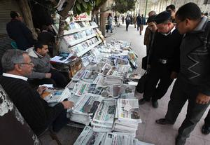 CAIRO, EGYPT - JANUARY 27:  Locals look at newspapers carrying reports and pictures of street protests on January 27, 2011 in Cairo, Egypt. Thousands of police are on the streets of the capital and hundreds of arrests have been made in an attempt to quell anti-government demonstrations.  (Photo by Peter Macdiarmid/Getty Images)